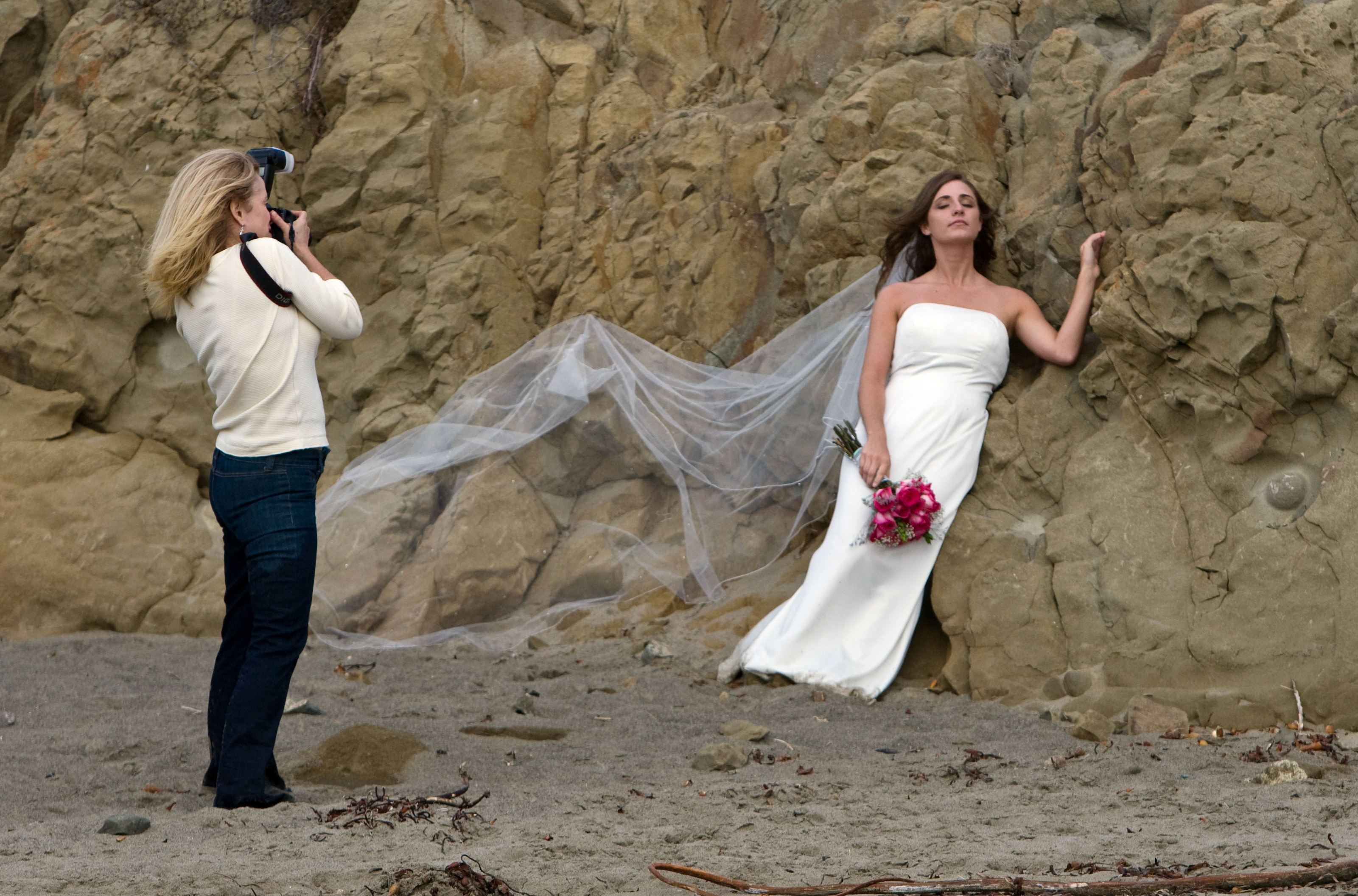 "1 of 4 Female photographer from Phoenix, Arizona, rehearses taking a critical wedding photo using her assistant here as a model, in later light on Morro Strand State Beach, Morro Bay, CA. 01 Nov. 2008. Michael ""Mike"" L. Baird, Canon 1D Mark III, 70-200mm f/2.8 IS handheld."